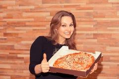Жизнерадостная женщина с большим пальцем руки удерживания пиццы ввер стоковые изображения