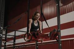 Жизнерадостная женщина crossfit делая тренировки abs на гимнастических кольцах стоковое фото rf