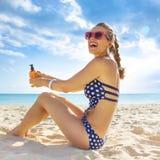 Жизнерадостная здоровая женщина в swimwear на береге моря с SPF стоковые изображения