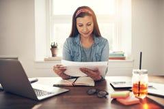Жизнерадостная коммерсантка делая обработку документов на рабочем месте в офисе Стоковые Фотографии RF