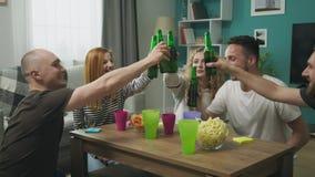 Жизнерадостная компания друзей выпивает пиво в уютной живущей комнате видеоматериал