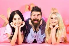 Жизнерадостная концепция утра Threesome ослабляя в утре Человек и женщины, друзья на усмехаясь положении сторон, розовой предпосы Стоковое фото RF