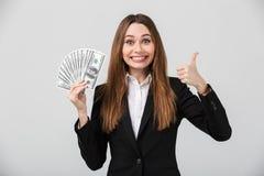 Жизнерадостная красивая дама брюнет показывая большой палец руки вверх и доллары пока смотрящ камеру изолировала стоковые изображения
