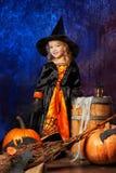 Жизнерадостная маленькая девочка в костюме ведьмы стоя рядом с woode Стоковое Фото