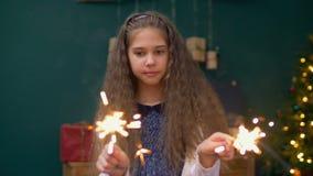 Жизнерадостная маленькая девочка играя с бенгальскими огнями на xmas видеоматериал