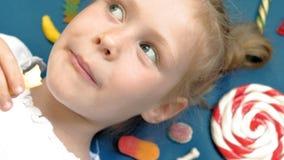 Жизнерадостная маленькая девочка лежит на голубой предпосылке с помадками r сток-видео