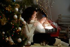 Жизнерадостная маленькая девочка празднуя рождество с ее матерью на hom стоковое фото rf
