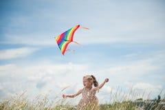 Жизнерадостная маленькая девочка при длинные волосы держа змея летания в поле на день лета солнечный Стоковые Фотографии RF