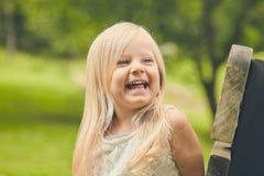 Жизнерадостная маленькая девочка смеясь над на стенде Стоковая Фотография RF