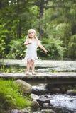 Жизнерадостная маленькая девочка стоя на деревянном мосте Стоковое Изображение