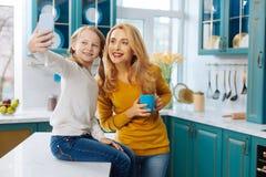 Жизнерадостная мать и дочь принимая selfies Стоковые Изображения RF