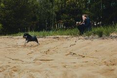 Жизнерадостная милая молодая женщина сидит, читает книгу и обнимает ее собаку на пляже Миниатюрный шнауцер с хозяйкой на озере стоковая фотография