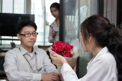 Жизнерадостная молодая азиатская женщина принимая букет красных роз от парня с завистливой сердитой предпосылкой женщины на день  Стоковое Изображение RF
