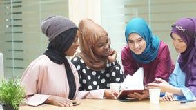 Жизнерадостная молодая аравийская книга чтения студенток в кафе видеоматериал