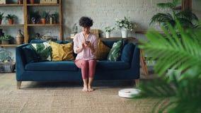 Жизнерадостная молодая дама поворачивает дальше робототехнический hoover и наслаждается автоматической чисткой сидя на софе и осл акции видеоматериалы