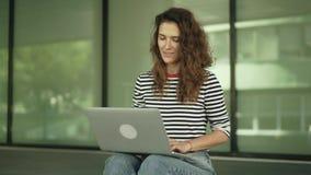 Жизнерадостная молодая женщина в видео джинсов вызывая к ее другу сидя снаружи видеоматериал