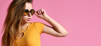 Жизнерадостная молодая женщина в солнечных очках против розовой предпосылки стоковое изображение