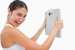 Жизнерадостная молодая женщина держащ маштабы стоковое изображение rf