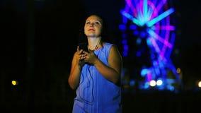 Жизнерадостная молодая женщина на набережной в наушниках слушая к музыке и танцуя против фона накаляя колеса ferris акции видеоматериалы