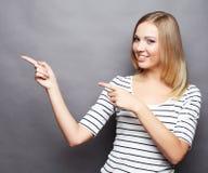 Жизнерадостная молодая женщина показывая copyspace, визуальное мнимое или некоторое стоковые изображения