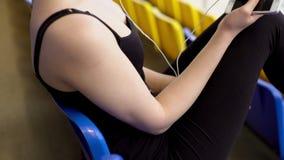 Жизнерадостная молодая женщина слушает к музыке на трибуне стадиона акции видеоматериалы
