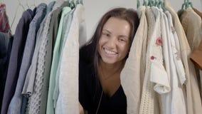 Жизнерадостная молодая женщина смотрит прищурясь от вешалок с одеждами в доме, смотрящ камеру, усмехаться и смеяться видеоматериал