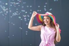 Жизнерадостная молодая женщина с красочной шляпой солнца на серой предпосылке лето seashells песка рамки принципиальной схемы пре стоковое фото