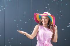 Жизнерадостная молодая женщина с красочной шляпой солнца на серой предпосылке лето seashells песка рамки принципиальной схемы пре стоковое фото rf