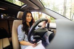 Жизнерадостная молодая женщина уча управлять свой собственный автомобилем стоковое изображение rf