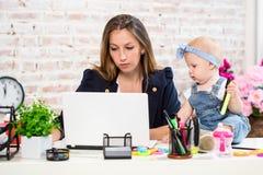 Жизнерадостная молодая красивая коммерсантка смотря компьтер-книжку пока сидящ на ее месте службы с ее маленькой дочерью Стоковое фото RF