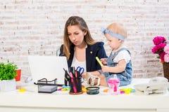 Жизнерадостная молодая красивая коммерсантка смотря компьтер-книжку пока сидящ на ее месте службы с ее маленькой дочерью Стоковое Изображение