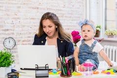 Жизнерадостная молодая красивая коммерсантка смотря компьтер-книжку пока сидящ на ее месте службы с ее маленькой дочерью Стоковые Изображения RF