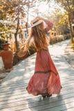 Жизнерадостная молодая модная женщина в шляпе имея потеху outdoors на заходе солнца стоковое изображение
