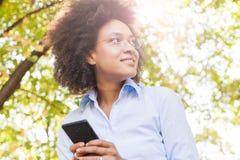 Жизнерадостная молодая чернокожая женщина используя телефон в природе стоковое фото rf