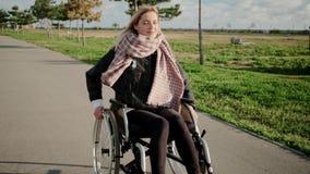 Жизнерадостная неработающая женщина управляет ее инвалидным экипажом в парке, прифронтовом взгляде сток-видео