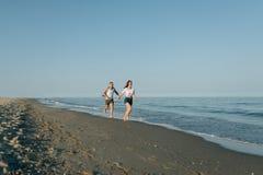 Жизнерадостная пара бежит на побережье моря Стоковые Фотографии RF