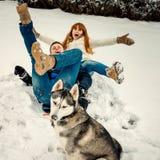 Жизнерадостная пара имеет потеху путем класть на снег пока сибирская лайка сидит в фронте их смешно стоковое изображение rf