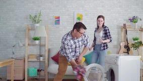 Жизнерадостная пара новобрачных приниманнсяые за рутинные работы по дому используя стиральную машину видеоматериал