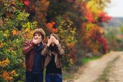 Жизнерадостная пара показывает эмоции человек и женщина в кожаных куртках и джинсах показывают сюрприз против предпосылки деревье стоковые фото