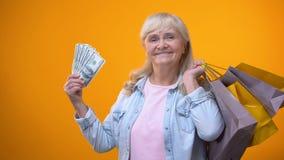Жизнерадостная пожилая женщина держа хозяйственные сумки и наличные деньги доллара, защиту интересов потребителя сток-видео