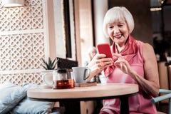 Жизнерадостная пожилая женщина удобно сидя в кафе стоковые фотографии rf