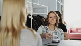 Жизнерадостная привлекательная девушка стоя на столе ` s кассира, беседуя с продавщицей и оплачивая для приобретений Продавец сток-видео