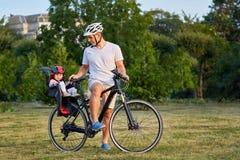 Жизнерадостная семья велосипед в парке Стоковая Фотография RF