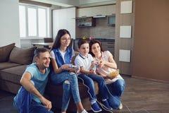 Жизнерадостная семья играет видеоигры в доме стоковое изображение