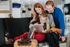 Жизнерадостная семья использует ноутбук на зале аэропорта стоковые изображения rf