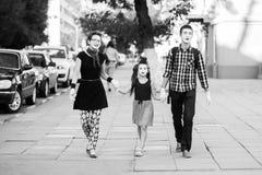 Жизнерадостная семья пантомим держа руки идя вниз с улицы Стоковая Фотография