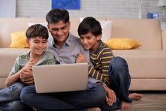 Жизнерадостная семья с компьтер-книжкой Стоковая Фотография