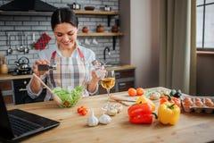 Жизнерадостная славная женщина сидит на таблице в кухне и положила специи в шар с салатом Она смотрит счастливой Женщина носит ри стоковые изображения rf