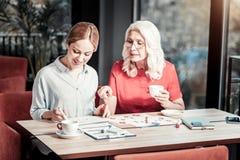Жизнерадостная старшая женщина указывая к документам молодого коллеги Стоковая Фотография RF