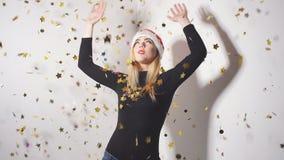 Жизнерадостная счастливая девушка в красной шляпе Санта Клаусе имея потеху пока танцующ под фейерверками confetti сток-видео